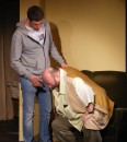 Ted (Colin Clark) has his first angina attack, whilst Jack (Michael Luke) stands over him.