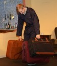 Henry Cockburn as Steve, struggling with some suitcases
